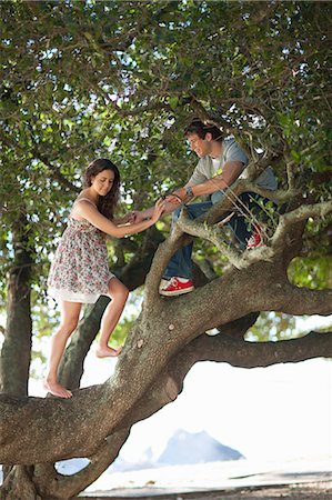 Couple climbing up a tree Stock Photo - Premium Royalty-Free, Code: 649-06432358