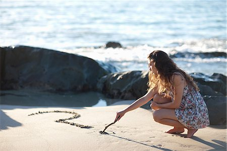 Woman drawing question mark in sand Stock Photo - Premium Royalty-Free, Code: 649-06432361