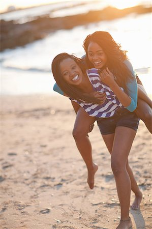 friend (female) - Woman carrying friend on beach Stock Photo - Premium Royalty-Free, Code: 649-06432381