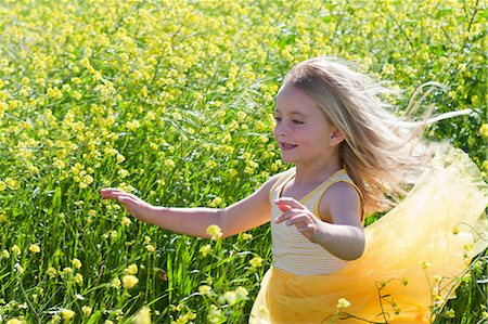 Smiling girl playing in field of flowers Stock Photo - Premium Royalty-Free, Code: 649-06432407