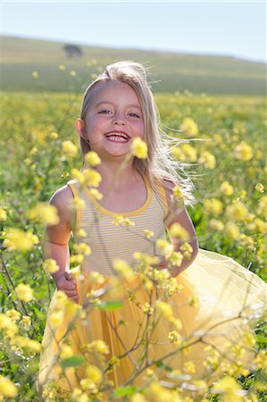 Smiling girl playing in field of flowers Stock Photo - Premium Royalty-Free, Code: 649-06432409