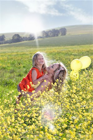 Sisters playing in field of flowers Stock Photo - Premium Royalty-Free, Code: 649-06432416