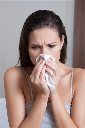 people coughing or sneezing - Woman blowing her nose on bed Stock Photo - Premium Royalty-Free, Code: 649-06432470