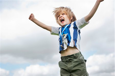 Boy with medals cheering outdoors Stock Photo - Premium Royalty-Free, Code: 649-06432508