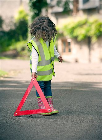 safety - Girl playing traffic worker on rural road Stock Photo - Premium Royalty-Free, Code: 649-06432501
