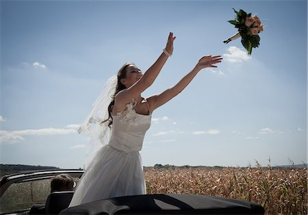 Newlywed bride tossing bouquet from car Stock Photo - Premium Royalty-Free, Code: 649-06432543