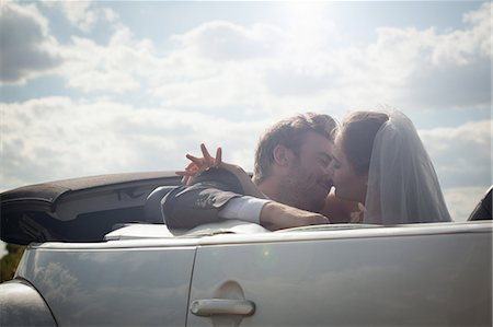 Newlywed couple about to kiss in a convertible Stock Photo - Premium Royalty-Free, Code: 649-06432555