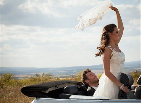 Newlywed couple riding in convertible Stock Photo - Premium Royalty-Free, Code: 649-06432557