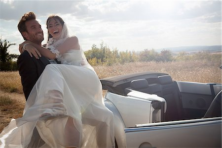 Newlywed groom carrying bride outdoors Stock Photo - Premium Royalty-Free, Code: 649-06432560