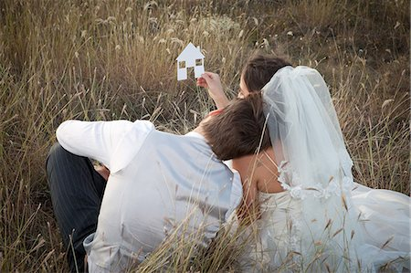 Newlywed couple holding a picture of a house Stock Photo - Premium Royalty-Free, Code: 649-06432577