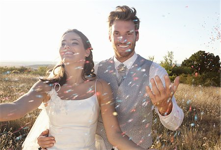 Newlywed couple walking in confetti Stock Photo - Premium Royalty-Free, Code: 649-06432594