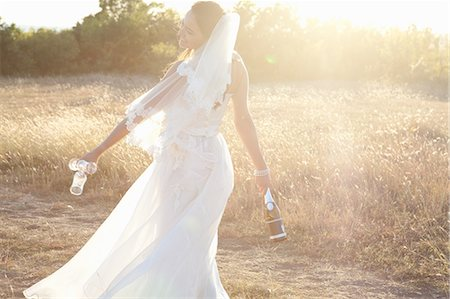 self indulgence - Newlywed bride carrying champagne Stock Photo - Premium Royalty-Free, Code: 649-06432595