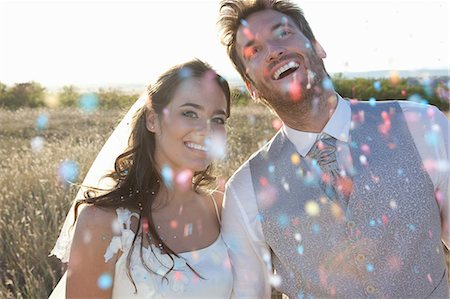 Newlywed couple walking in confetti Stock Photo - Premium Royalty-Free, Code: 649-06432593