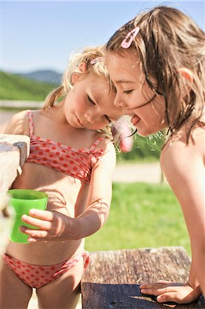 Children playing with water in backyard Stock Photo - Premium Royalty-Free, Code: 649-06432606