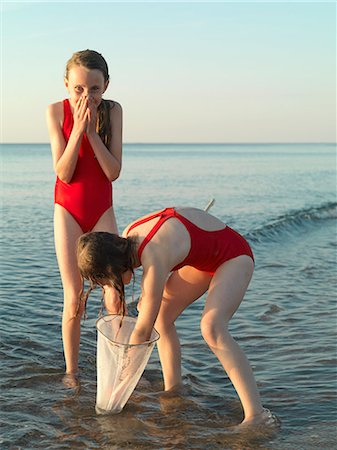 preteen bathing suit - Girls fishing in shallow water Stock Photo - Premium Royalty-Free, Code: 649-06432692
