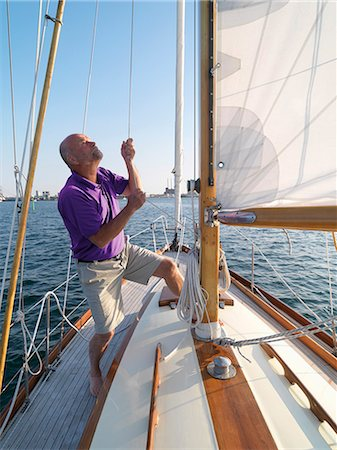 sailboat  ocean - Man adjusting rigging on sailboat Stock Photo - Premium Royalty-Free, Code: 649-06432711