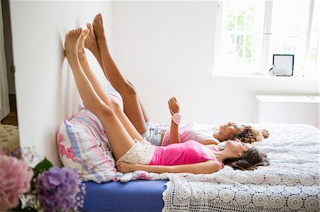 Women relaxing on bed together Stock Photo - Premium Royalty-Free, Code: 649-06432899