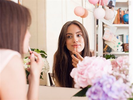 Woman applying make up in mirror Stock Photo - Premium Royalty-Free, Code: 649-06432941