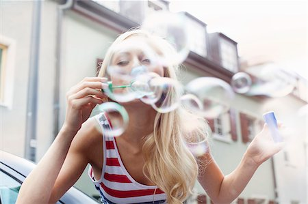 Smiling woman blowing bubbles outdoors Stock Photo - Premium Royalty-Free, Code: 649-06432956