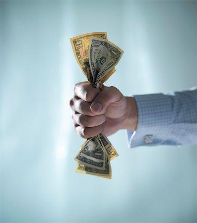 Close up of fist clenching dollar bills Stock Photo - Premium Royalty-Free, Code: 649-06432984