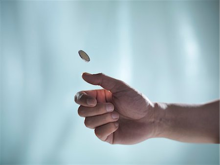 Close up of hand tossing coin Stock Photo - Premium Royalty-Free, Code: 649-06432987