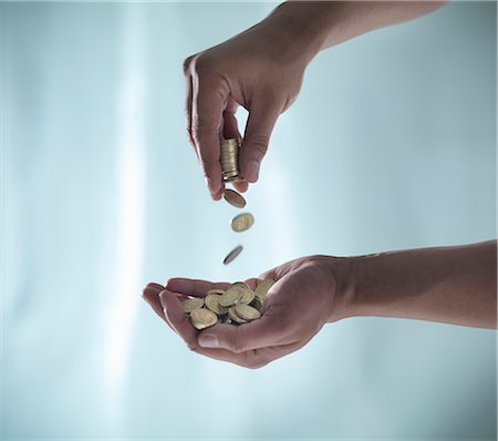 savings - Hands playing with pile of coins Stock Photo - Premium Royalty-Free, Code: 649-06432981