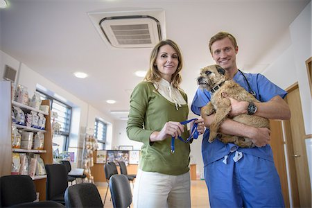 Veterinarian holding dog in lobby Stock Photo - Premium Royalty-Free, Code: 649-06433057