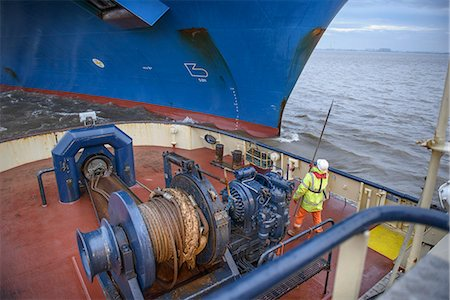 ships at sea - Tugboat worker catching rope on deck Stock Photo - Premium Royalty-Free, Code: 649-06433086