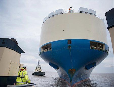 ships at sea - Tugboat sailing by large ship Stock Photo - Premium Royalty-Free, Code: 649-06433088