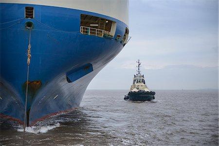 ships at sea - Tugboat sailing by large ship Stock Photo - Premium Royalty-Free, Code: 649-06433089