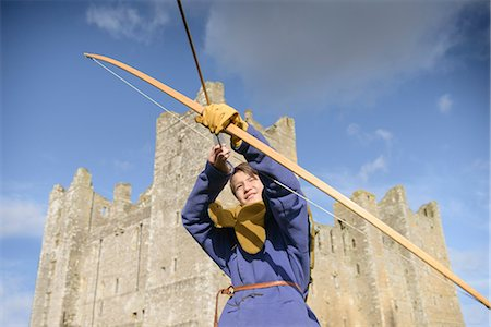 Student in period dress shooting arrow Stock Photo - Premium Royalty-Free, Code: 649-06433138