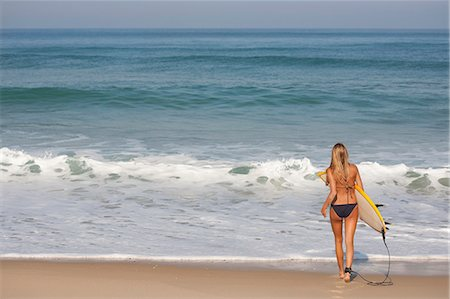 Woman carrying surfboard on beach Stock Photo - Premium Royalty-Free, Code: 649-06433264
