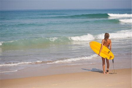 Woman carrying surfboard on beach Stock Photo - Premium Royalty-Free, Code: 649-06433275