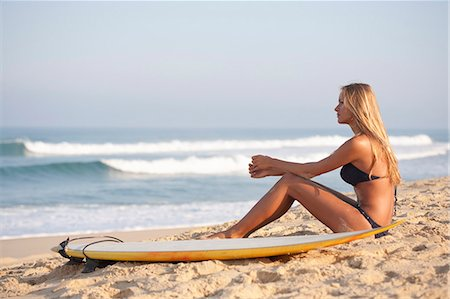Woman sitting with surfboard on beach Stock Photo - Premium Royalty-Free, Code: 649-06433278