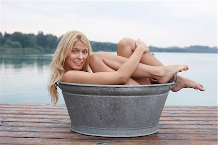 Woman sitting in bucket on wooden deck Stock Photo - Premium Royalty-Free, Code: 649-06433288