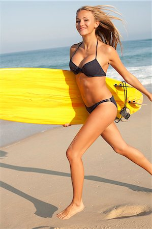 Woman carrying surfboard on beach Stock Photo - Premium Royalty-Free, Code: 649-06433281