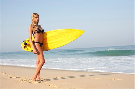 Woman carrying surfboard on beach Stock Photo - Premium Royalty-Free, Code: 649-06433282