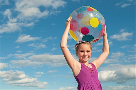 Smiling girl holding beach ball outdoors Stock Photo - Premium Royalty-Free, Code: 649-06433485