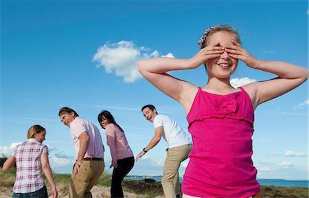 Family playing hide and seek outdoors Stock Photo - Premium Royalty-Free, Code: 649-06433491