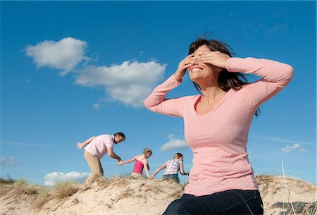 Family playing hide and seek outdoors Stock Photo - Premium Royalty-Free, Code: 649-06433492
