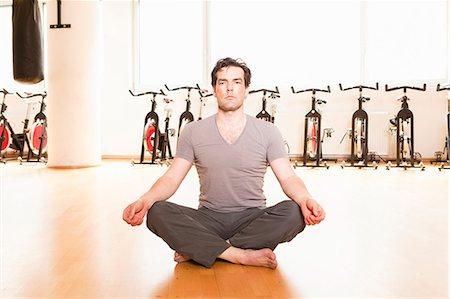 Man meditating on mat at gym Stock Photo - Premium Royalty-Free, Code: 649-06433566