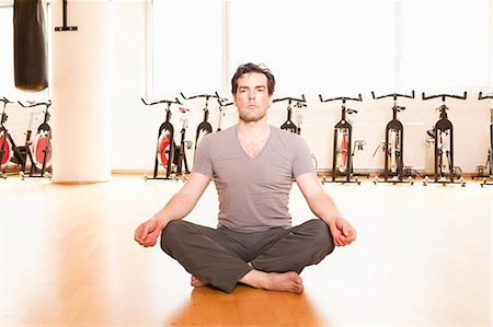 Man meditating on mat at gym Stock Photo - Premium Royalty-Free, Code: 649-06433566