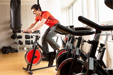 Man using stationary bicycle at gym Stock Photo - Premium Royalty-Free, Code: 649-06433569