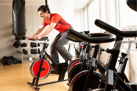 Man using stationary bicycle at gym Stock Photo - Premium Royalty-Free, Code: 649-06433569