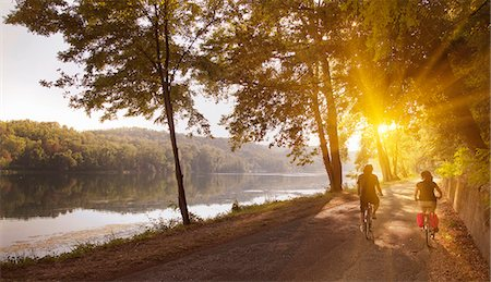 sun - Couple riding bicycles by river bank Stock Photo - Premium Royalty-Free, Code: 649-06433680