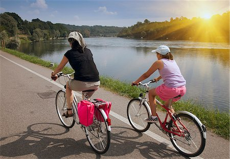 recreation - Women riding bicycles by river bank Stock Photo - Premium Royalty-Free, Code: 649-06433683