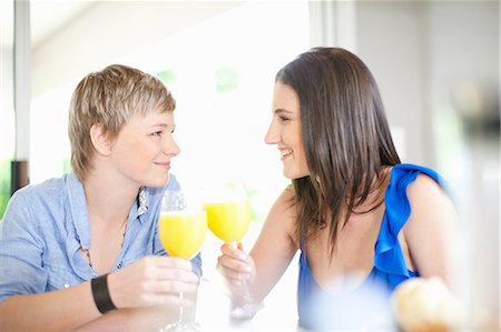 Lesbian couple having orange juice Foto de stock - Sin royalties Premium, Código: 649-06488403