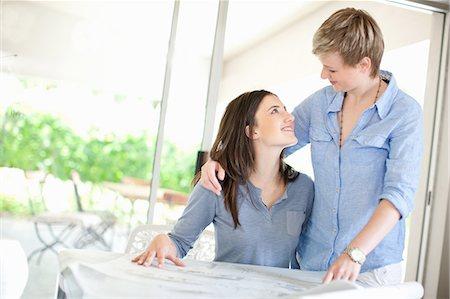 Lesbian couple reading blueprints Stock Photo - Premium Royalty-Free, Code: 649-06488416