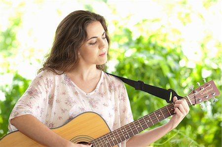 Woman playing guitar outdoors Stock Photo - Premium Royalty-Free, Code: 649-06488494
