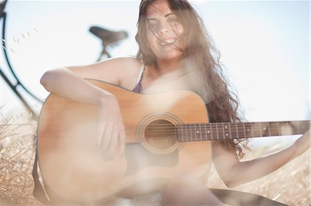 Woman playing guitar in tall grass Stock Photo - Premium Royalty-Free, Code: 649-06488529